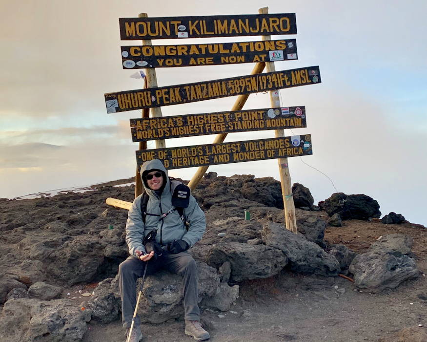 Jeff Crow, material planner in the Defense Logistics Agency Troop Support's Industrial Hardware supply chain, rests on a rock under the sign that marks his accomplishment in climbing Tanzania's Mount Kilimanjaro during a trip in December 2018. Crow said the climb was always on his bucket list, and he is happy to have been able to take the time off to make the journey. (Photo courtesy of Jeff Crow)