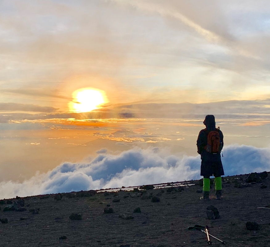 Jeff Crow, material planner in the Defense Logistics Agency Troop Support's Industrial Hardware supply chain, stands atop Tanzania's Mount Kilimanjaro, watching the sunset from above the clouds during a trip in December 2018. Crow and his fellow trekkers summited the mountain after a full day of climbing, and took advantage of favorable weather to summit early and see the sunset. (Photo courtesy of Jeff Crow)