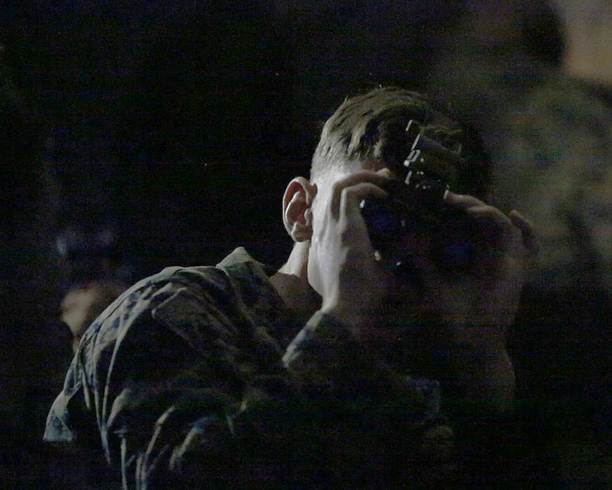 A Marine peers through the lens of the Squad Binocular Night Vision Goggles during new equipment training in December 2018 at Camp Lejeune, North Carolina. (U.S. Marine Corps photo by Joseph Neigh)