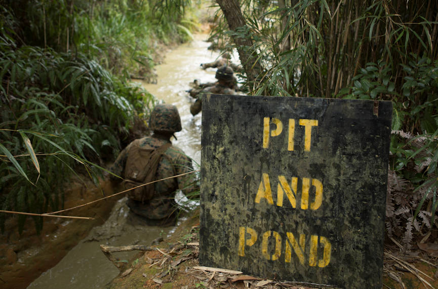 "Marines with Communications Company, Headquarters Regiment, 3rd Marine Logistics Group, begin their decent into the muddy water during an obstacle in the Endurance Course on Camp Gonsalves, Okinawa, Japan, Feb. 16, 2018. The ""Pit and Pond"" is an obstacle in the E-Course made up of low crawls through water-filled trenches and under walkways in the Jungle Warfare Training Center. BJSC is designed to teach Marines how to operate in a jungle environment. (U.S. Marine Corps photo by Lance Cpl. Jamin M. Powell)"