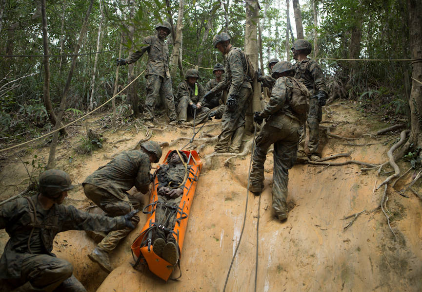 Marines with Communications Company, Headquarters Regiment, 3rd Marine Logistics Group, slide a simulated victim down a hill at the Endurance Course on Camp Gonsalves, Okinawa, Japan, Feb. 16, 2018. The E-Course is the culminating event in the Basic Jungle Skills Course, consisting of obstacles scattered through the hill-riddled jungle. BJSC is designed to teach Marines how to operate in a jungle environment. (U.S. Marine Corps photo by Lance Cpl. Jamin M. Powell)