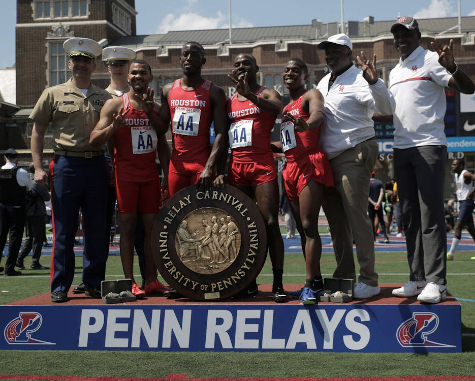 Maj. John Meixner, the commanding officer of Recruiting Station Harrisburg in New Cumberland, Pennsylvania, and Capt. Daniel Comito, the Officer Selection Officer at Officer Selection Station Philadelphia, present John Lewis III, Mario Burke, Nicholas Alexander and Cameron Burrell, winners of College Men's 4x100 meter Championship of America Invitational, their award during the Penn Relays at Franklin Field at the University of Pennsylvania April 28, 2018. Marines partnered with and attended the 124th Penn Relays to foster positive relationships with student athletes and coaches and to educate the track and field community on opportunities within the Marine Corps. The athletes are from the University of Houston. Collectively, they ran 400 meters in 38.95 seconds. (U.S. Marine Corps photo by Lance Cpl. Naomi Marcom)