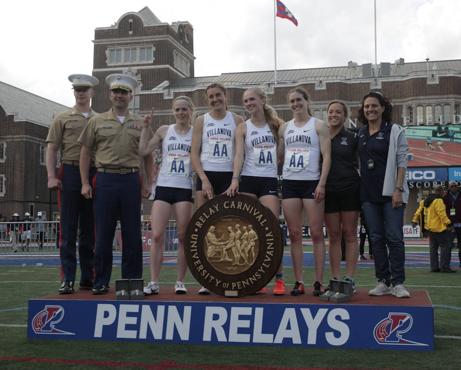 Maj. John Meixner, the commanding officer of Recruiting Station Harrisburg in New Cumberland, Pennsylvania, and Capt. Daniel Comito, the Officer Selection Officer at Officer Selection Station Philadelphia, present Stofra Cleirigh Buttner, Rachel McArthur, Kelsey Margey and McKenna Keegan, winners of College Women's 4x800 meter Championship of America Invitational, their award during the Penn Relays at Franklin Field at the University of Pennsylvania April 28, 2018. (U.S. Marine Corps photo by Lance Cpl. Naomi Marcom)
