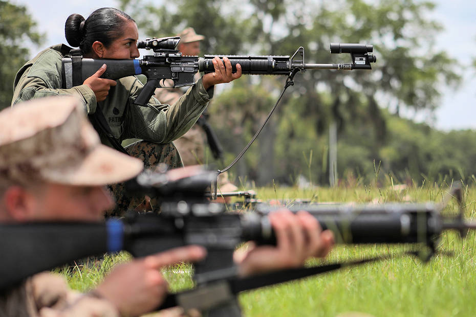 U.S. Marine Corps Staff Sgt. Estefania Patino, Primary Marksmanship Instructor, corrects the rifle combat optic (RCO) of a recruit's weapon during grass week while other recruits continue with their shooting on June 6, 2018, on Parris Island, S.C. The purpose of grass week is to teach recruits shooting positions and weapon safety rules for Table 1 and 2. (U.S. Marine Corps photo by Sgt. Dana Beesley)