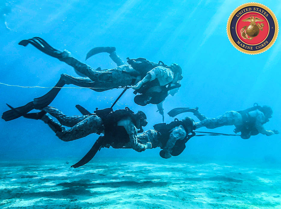 U.S. Marines with Maritime Raid Force (MRF), 26th Marine Expeditionary Unit (MEU), swim underwater during dive training in Aqaba, Jordan, July 8, 2018. The Marines are deployed aboard the USS Iwo Jima with the U.S. 5th Fleet area of operations in support of naval operations to ensure maritime stability and security in the central region, connecting the Mediterranean and the Pacific through the western Indian Ocean and three strategic choke points. (Image created by USA Patriotism! from U.S. Marine Corps photo by Cpl. Jon Sosner)
