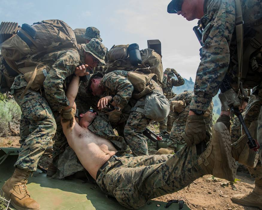 Marines with Kilo Company, 3rd Battalion, 5th Marine Regiment, 1st Marine Division, lift a simulated casualty onto a litter during a long distance hike in the Sierra Nevada Mountains during Mountain Training Exercise (MTX) 4-18 aboard Mountain Warfare Training Center Bridgeport, California on July 30, 2018. (U.S. Marine Corps photo by Cpl. Adam Dublinske)