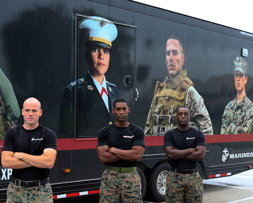 U.S. Marine Corps Sgt. Travis Lindsay (left), SSgt. John Liddell (middle), and Sgt. Quemaine Tolar (right), members of the 8th Marine Corps District Mobile Marketing Team, pose for a group photo in front of the Enhanced Marketing Vehicle on Naval Air Station Joint Reserve Base, Fort Worth, Texas on October 17, 2018. The MMT is responsible for augmenting local recruiter efforts throughout the District's area of operations spanning across 13 states. (U.S. Marine Corps photo by Lance Cpl. Desmond Andrews)