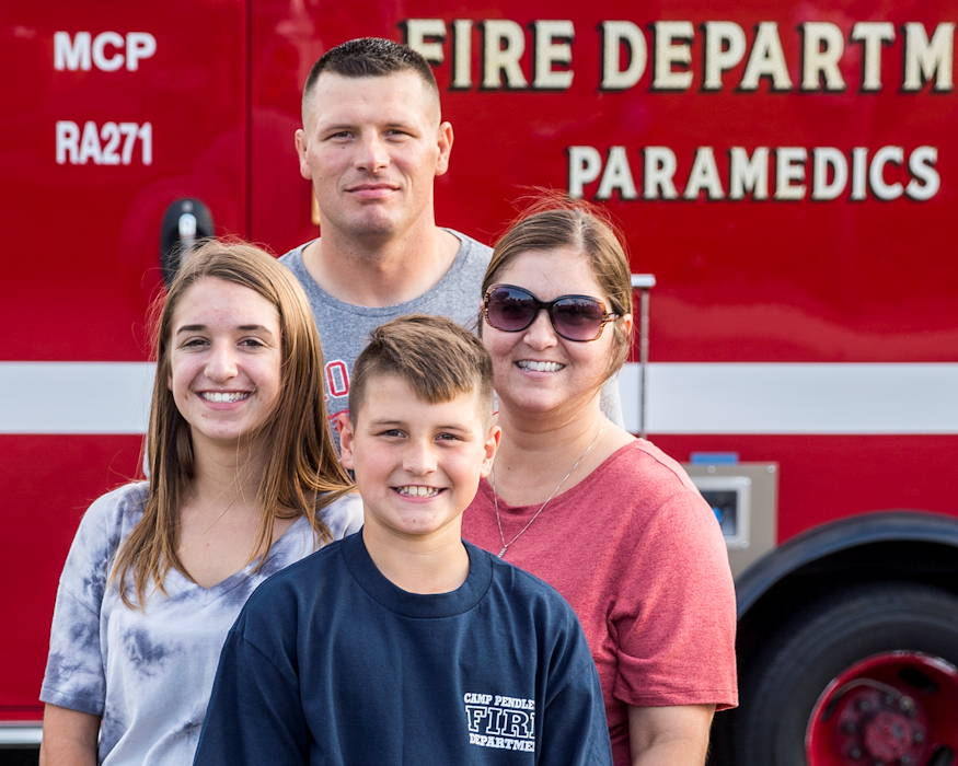 Eleven year-old Gavin Zeek (center) and his family pose for a photo at the National Night Out event at the De Luz Community Center at Marine Corps Base Camp Pendleton, California on October 2, 2018. During the event, Gavin was presented with a certificate of appreciation from the Camp Pendleton Fire Department for assisting his friends and neighbors in evacuating from the South De Luz Housing area during the Pendleton Complex Fire on July 7, 2018. (U.S. Marine Corps photo by Cpl. Dylan Chagnon)