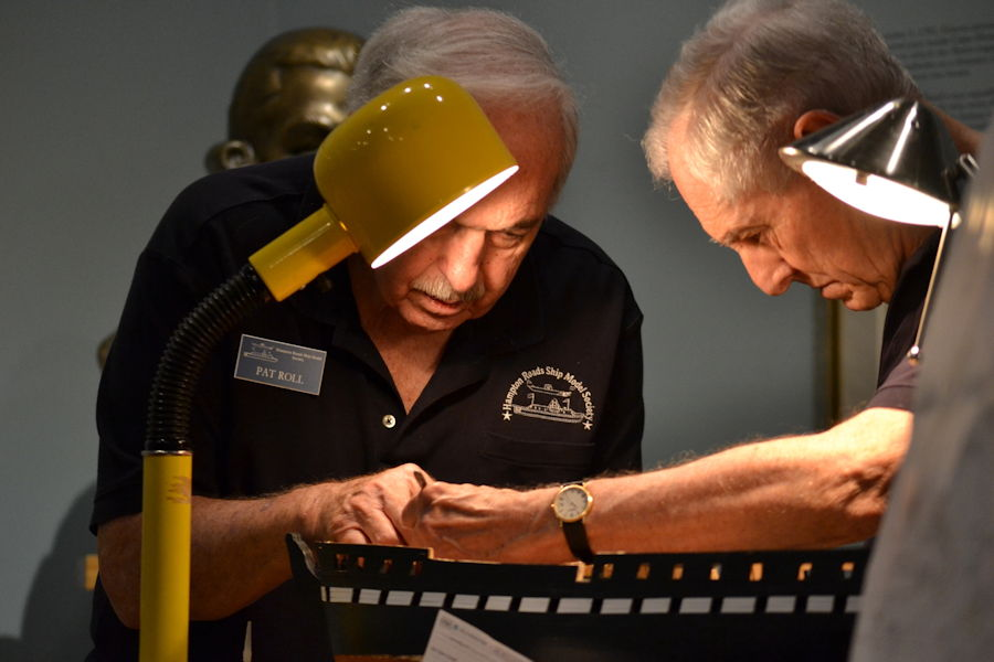 June 28, 2018 - Volunteer model shipbuilders from the Hampton Roads Ship Model Society, work on a wooden model of the USS Constitution. Pictured are resident model shipbuilders Pat Roll (left) and Lee Martin (right) working at their workbench in the gallery of the Hampton Roads Naval Museum. Both have been volunteering at the Hampton Roads Naval Museum for a combined eleven years. (US Navy Photo by Civilian Public Affairs Officer Max Lonzanida)