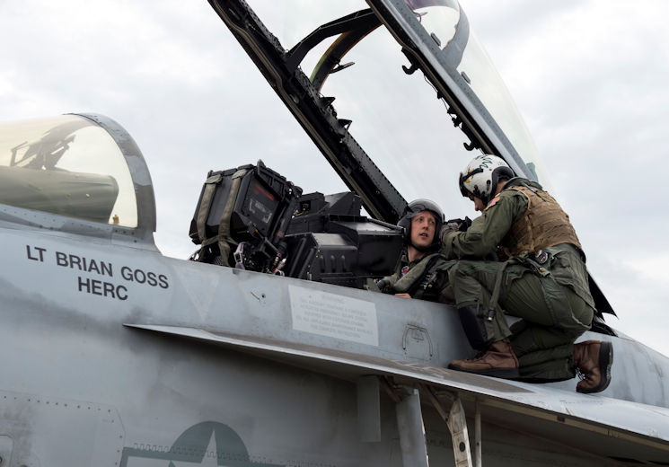 June 20, 2017 - Lt. Jace Mirmak, Carrier Air Wing One Staff Landing Signal Officer, familiarizes Dr. Marcus Tepaske, Office of Naval Research Global science advisor to U.S. Fleet Forces Command, with the controls of an F/A-18E/F Super Hornet assigned to Strike Fighter Squadron (VFA) 211, prior to an orientation flight. Science advisors are civilian scientists, engineers and technologists who serve at a Joint, Navy or Marine Corps command as the senior liaison with science and technology organizations in government, academia and industry. (U.S. Navy photo by John F. Williams)