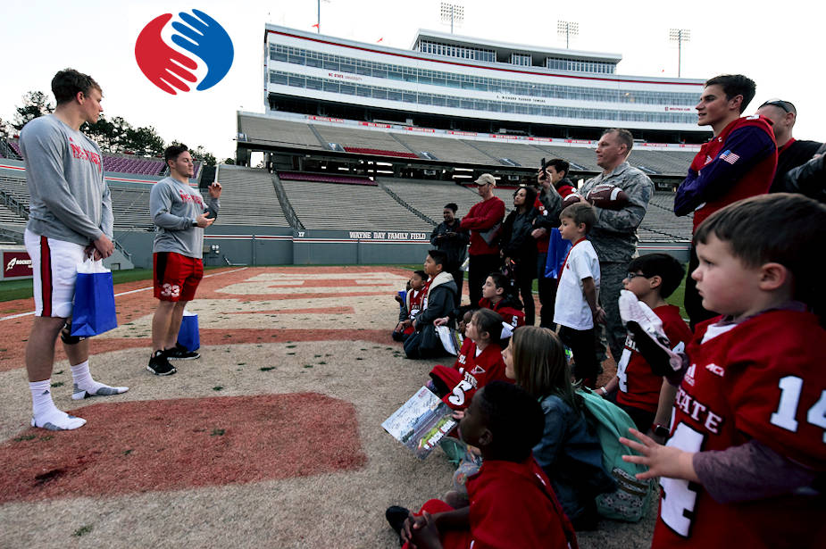 Ryan Finley (left) and Brady Bodine, North Carolina State University quarterback and running back, talk to military families during an Operation Teammate event, March 23, 2018, at NC State University in Raleigh, North Carolina. Bodine, whose father serves in the U.S. Marine Corps, shared his experiences of growing up in a military family and how he dealt with the challenges of separation. (Image created by USA Patriotism! from U.S. Air Force photo by Staff Sgt. Brittain Crolley)