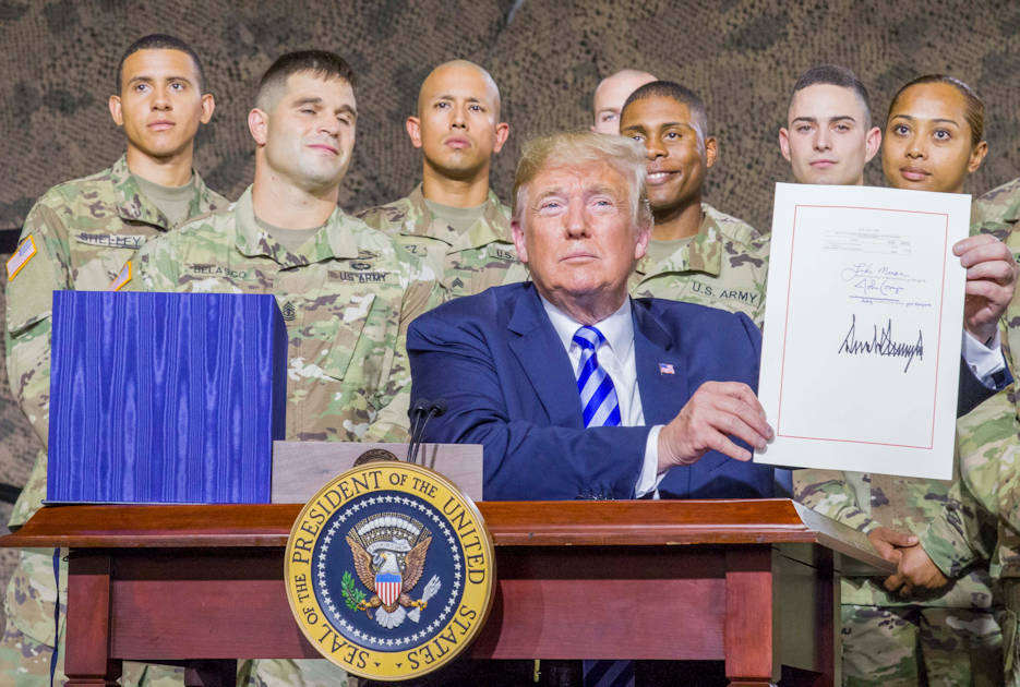 August 13, 2018 - President Donald J. Trump shows the signed copy of the National Defense Authorization Act of 2019 at Fort Drum, NY with Soldiers from the U.S. Army 10th Mountain Division behind him. (U.S. Army photo by Sgt. Thomas Scaggs)