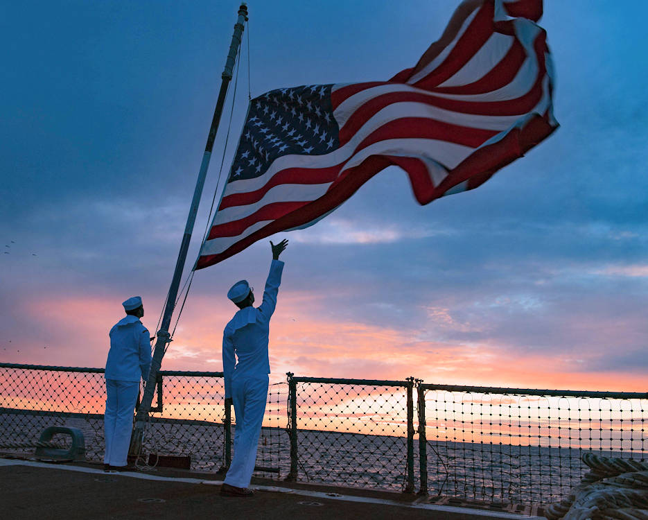 August 5, 2018 - Information Systems Technician 3rd Class Jesse Torres (left) and Electronics Technician 3rd Class Cory Stackhouse lower the American flag during evening colors aboard the Arleigh Burke-class guided-missile destroyer USS Winston S. Churchill (DDG 81), while conducting naval operations in the U.S. 6th Fleet area of operations in support of U.S. national security interests in Europe and Africa. (U.S. Navy photo by Mass Communication Specialist 2nd Class Evan Thompson)