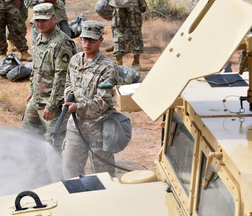 Spc. Jorge Castillo, assigned to Battery A, 3rd Battalion, 43rd Air Defense Artillery Regiment, 11th Air Defense Artillery Brigade, practices decontaminating a truck during chemical, biological, radiological and nuclear decontamination training at Fort Bliss, Texas, September 7, 2018. Castillo received a promotion to sergeant later in the day. (U.S. Army photo by Wendy Brown, Fort Bliss Garrison Public Affairs)