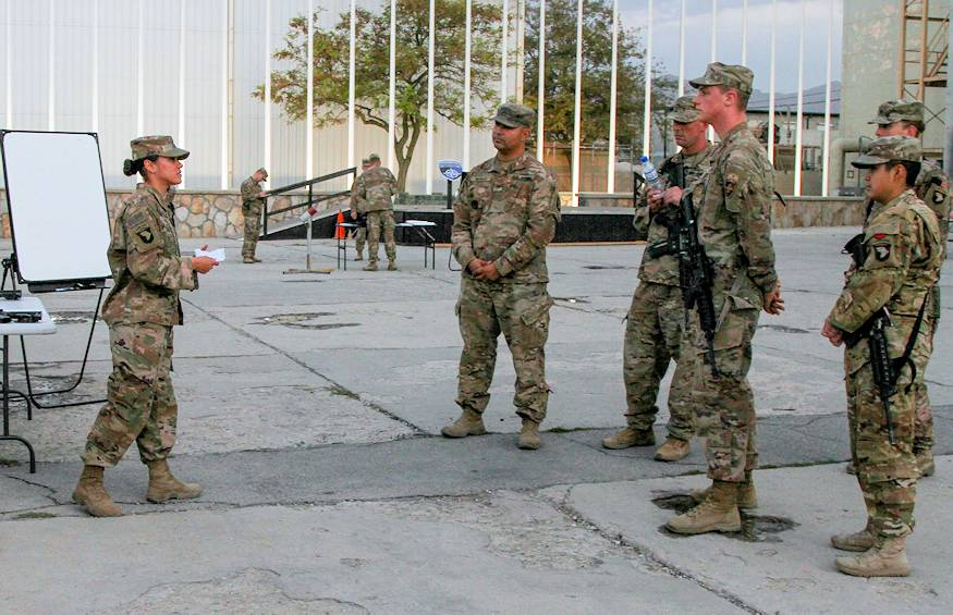Sergeant Crystal Falcon (left), the support operations transportation contracting officer representative for the 101st Resolute Support Sustainment Brigade, speaks to her audience, instructing them on the proper way to determine the grid coordinates of a point on a military map, at Bagram Airfield, Afghanistan, Sept. 27, 2018. The Junior Leader Certification program is something that Sgt. 1st Class Billy Scott, the sustainment automation support management office noncommissioned officer in charge, and Master Sgt. Mark Gomez, the signal support systems chief for the brigade and native of San Antonio, Texas, created in order to assist junior enlisted Soldiers in getting a head start on their development as future leaders in the Army, focusing on the operational domain of the Army Leadership Development Model. (U.S. Army Photo by Staff Sgt. Caitlyn Byrne, 101st Sustainment Brigade PAO)