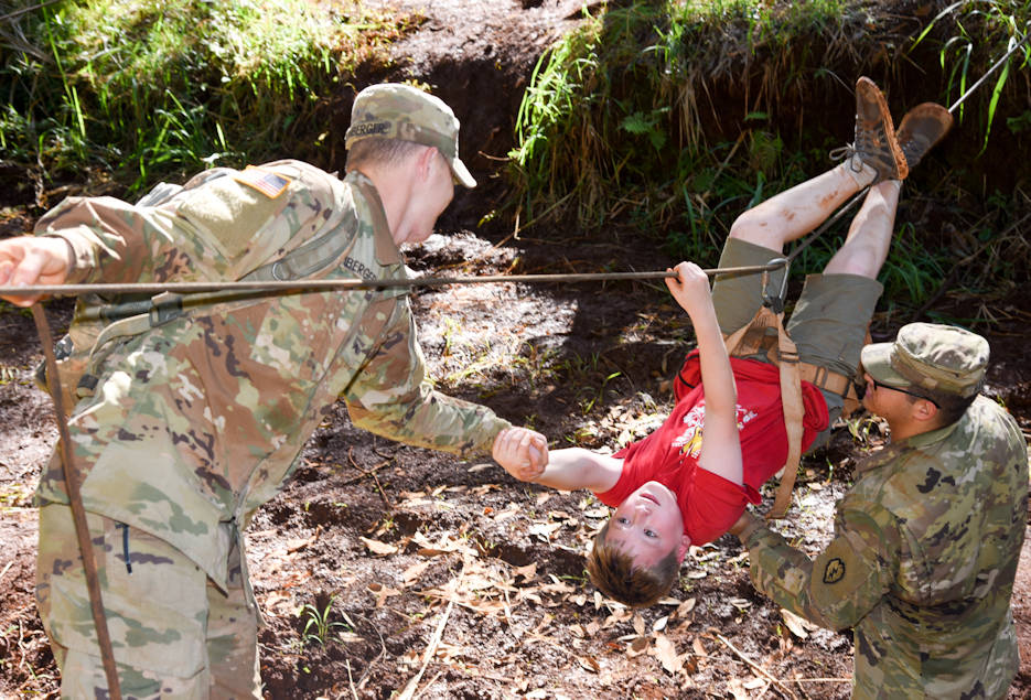 December 28, 2017 - Nathaniel Beckstrom, an Arrow of Light Cub Scout from Pack 166 on Schofield Barracks, Hawaii, is helped across a rope line by Spc. Johnie Marquez (right) and Pvt. John Momberger (left), Soldiers from 2nd Squadron, 14th Cavalry Regiment, 2nd Infantry Brigade Combat Team, 25th Infantry Division during Schofield Days. This event is an Army community relations event where Soldiers conduct, teach and share techniques they use on a daily basis to serve and protect the nation. (U.S. Army photo by Staff Sgt. David N. Beckstrom, 2nd Infantry Brigade Combat Team, 25th Infantry Division)