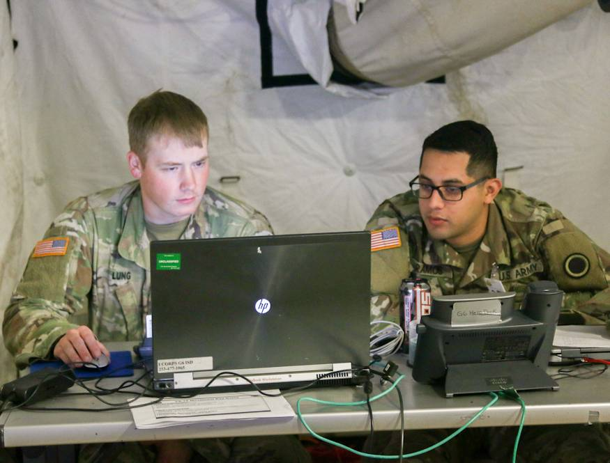 Spc. Aaron Lung and Spc. Armando Ramos from the Intelligence and Support Company conduct helpdesk operations by trouble shooting issues that Soldiers are having in the command operations information center during Warfighter Exercise 19-1. WFX 19-1 is a tactical command post exercise that was held from October 2-10, 2018 on Joint Base Lewis-McChord that included units from across America's First Corps and attached components from the Army National Guard. This exercise gave the units the opportunity to hone their skills and test their capabilities through simulated battle drills. (U.S Army photo by Sgt. William Brown)