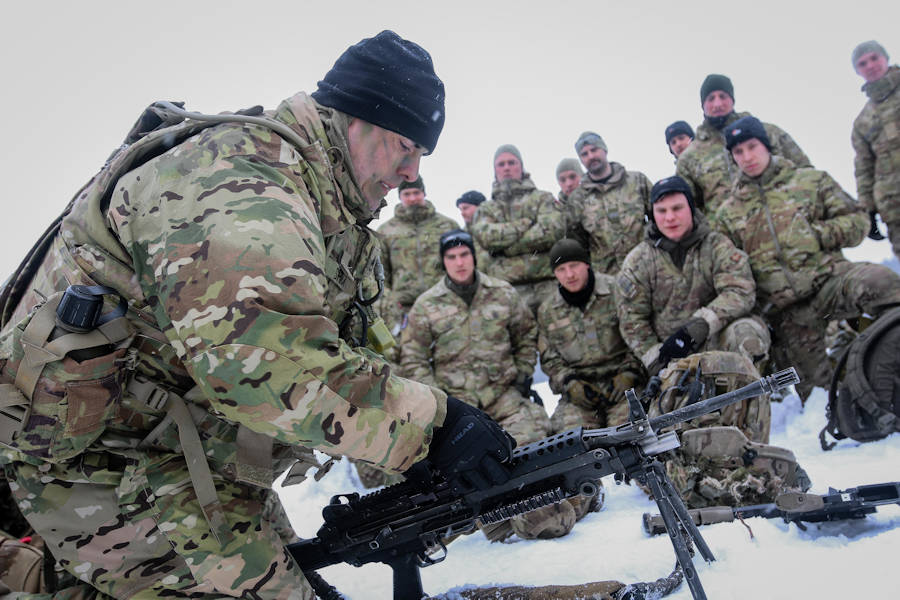 U.S. Army Staff Sgt. Jason Shick (left), an Erie, Pennsylvania native and a chemical, biological, radiological, and nuclear specialist with the 82nd Brigade Engineer Battalion, 2nd Armored Brigade Combat Team, 1st Infantry Division, teaches Danish soldiers of the Danish Vidar Company, Guard Hussars Regiment, how to use an M249 Light Machine Gun during a multinational weapons training session in Tapa, Estonia, March 10, 2018 as part of a rapid response readiness exercise in support of Atlantic Resolve. (U.S. Army photo by Spc. Hubert D. Delany III, 22nd Mobile Public Affairs Detachment)
