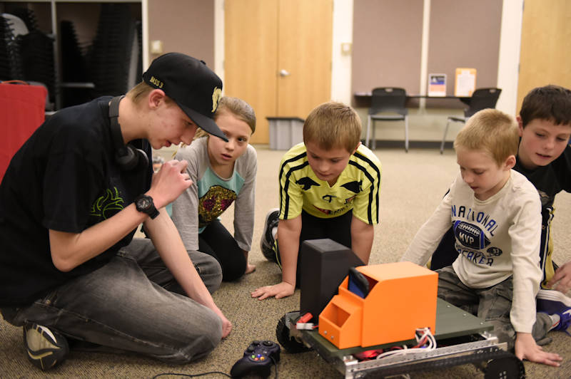 "Sixteen-year-old South High School student Brandon Schwab, demonstrates his team's robot to 5th grade students during an exhibition at the Laramie County Library ""Discover Space, A Cosmic Journey"" event, Jan. 12, 2018. Nine 8th to 10th grade students are involved with the STARBASE-sponsored activity. (Wyoming Army National Guard photo by Sgt. 1st Class Jimmy McGuire)"
