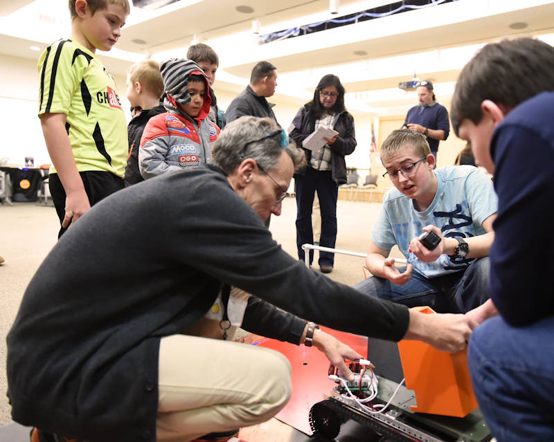 "Kade Smith, a 16-year-old East High School student and STARBASE Deputy Director and First Tech Challenge Coach Mark Nowotny troubleshoot a malfunction with a robot as 5th grade students watch during an exhibition at the Laramie County Library ""Discover Space, A Cosmic Journey"" event, Jan. 12, 2018. Nine 8th to 10th grade students are involved with the STARBASE-sponsored activity. (Wyoming Army National Guard photo by Sgt. 1st Class Jimmy McGuire)"