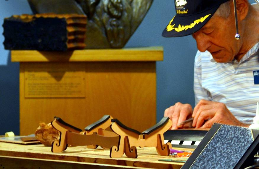 Lee Martin, a volunteer model ship builder who was in the gallery working on a model of the USS Constitution, the world's oldest commissioned naval vessel still afloat, at the Hampton Roads Naval Museum on September 27, 2018, when Tony D'Angelo, a museum volunteer, graciously loaned him a piece of red oak from the USS Constitution. (U.S. Navy photo by Civilian Public Affairs Officer Max Lonzanida)