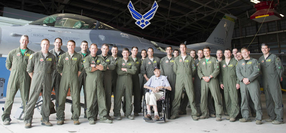 World War II pilot and combat veteran, Mr. Lyndol Palin poses with the 134th Fighter Squadron in front of a Green Mountain Boy F-16 at the 158th Fighter Wing. Palin spent an afternoon engaging with the 134th Fighter Squadron at the Vermont Air National Guard Base, S. Burlington, Vermont on June 3, 2018. (Image created by USA Patriotism! from U.S. Air National Guard Photo by Staff Sgt. Jonathon Alderman)