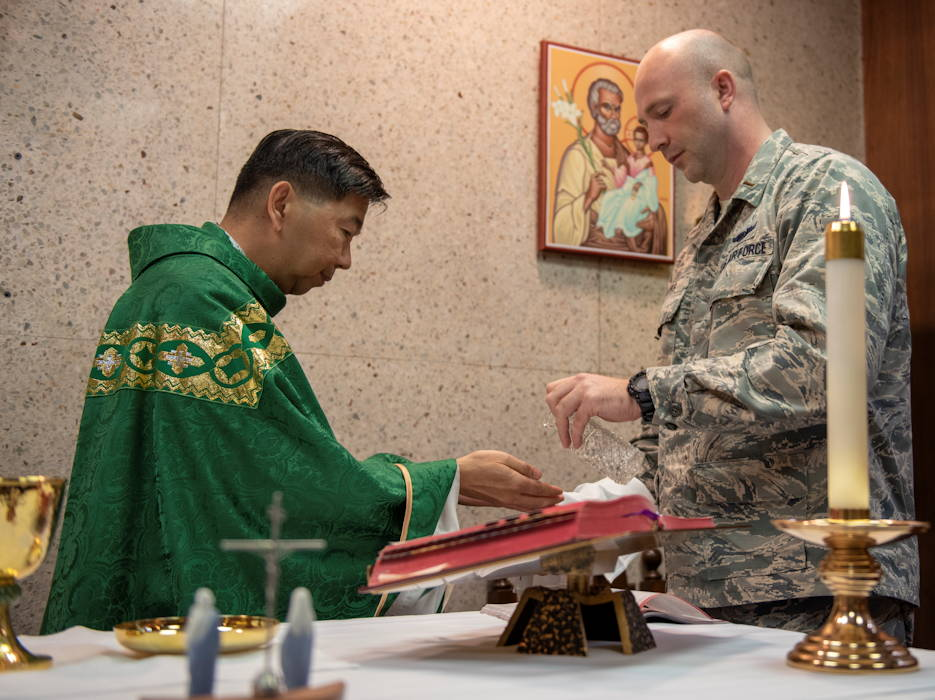 July 2, 2019 - 2nd. Lt. Madison Hayes, Air Force Reserve Command chaplain candidate out of Robins Air Force Base, Georgia, assists Capt. Antonio Rigonan, 374th Airlift Wing chaplain, with Catholic Mass at Yokota Air Base, Japan. Hayes, like all chaplain candidates, go through the Chaplain Candidate Intensive Internship program, a program designed to give candidates the opportunity to work with active-duty chaplains at various installations to gain the experience needed to operate and succeed as chaplains in the U.S. Air Force. (U.S. Air Force photo by Senior Airman Matthew Gilmore)