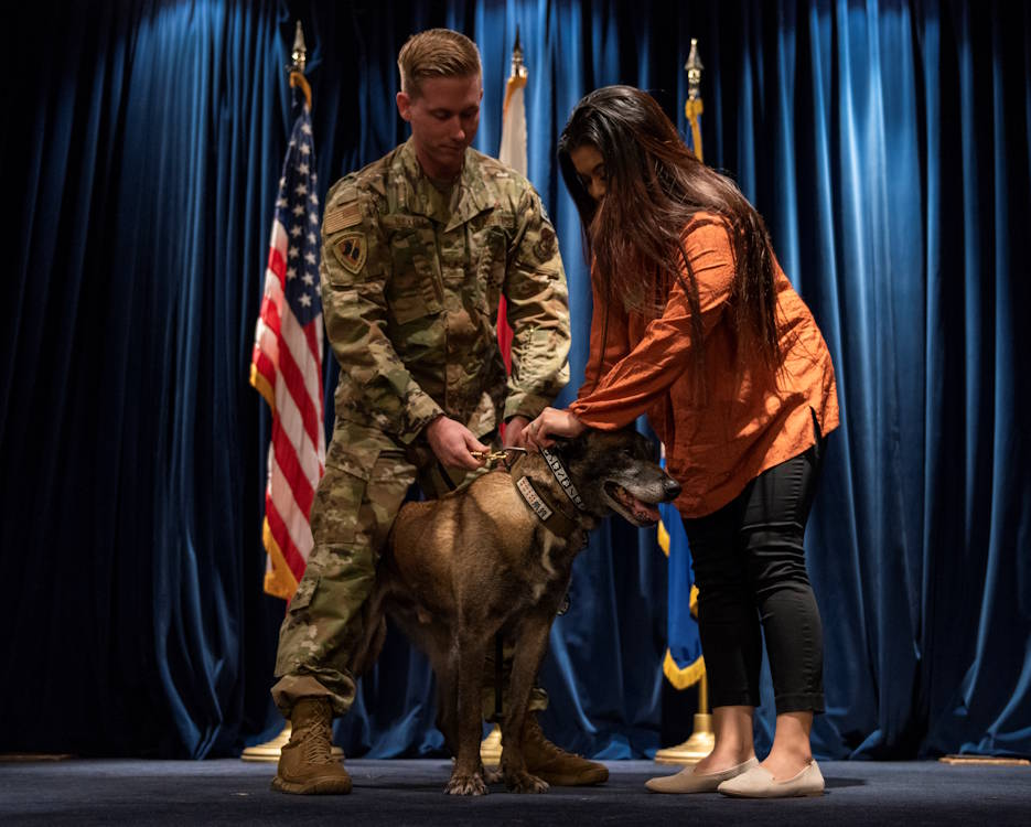 October 17, 2019 - Staff Sgt. Cody Nickell, 374th Security Forces Squadron military working dog handler, and his wife Monikka, perform the ceremonial collar swap signaling the end of military working dog Topa's service at a retirement ceremony at Yokota Air Base, Japan. Beginning his service in 2012, Topa has served as a proud member of military working dog teams, putting his patrol and explosives detection training to the test in the constant defense of YAB. (U.S. Air Force photo by Senior Airman Matthew Gilmore)