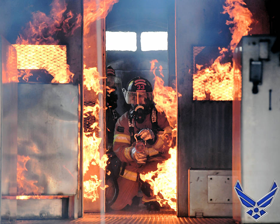 June 4, 2019 - A Keesler Air Force Base firefighter uses a hand-held hose to extinguish a fire inside a mock C-123 Provider training device during an aircraft rescue fire fighting training on Keesler AFB, Mississippi. (Image created by USA Patriotism! from U.S. Air Force photo by Kemberly Groue)