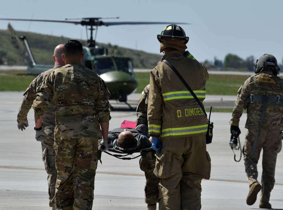 A Fairchild medical response team carries a fellow airman role-playing as an injured bystander during the Major Action Response Exercise (MARE) at Fairchild Air Force Base, Washington on May 9, 2019. The MARE included several simulated aircraft crashes, mock casualties and three fires to equip Team Fairchild for the upcoming Inland Northwest SkyFest Open House. (U.S. Air Force photo by Airman Kiaundra Miller)
