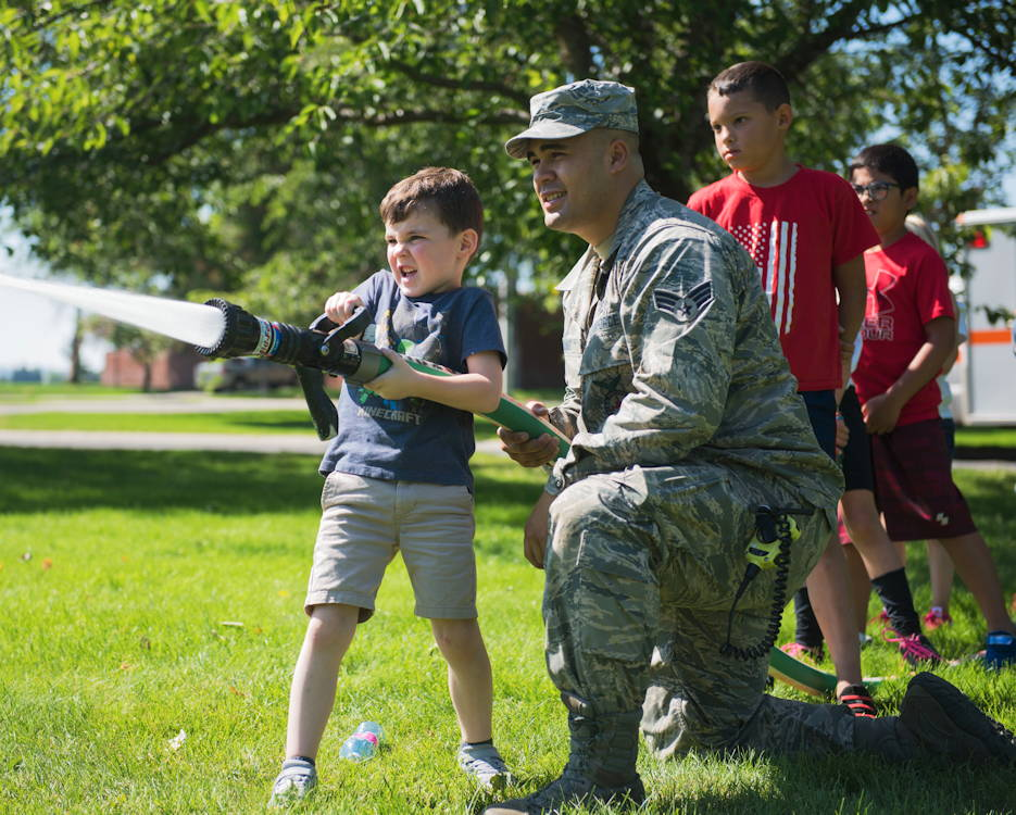 July 25, 2019 - U.S. Air Force Senior Airman Isaiah Raiano, 92nd Civil Engineer Squadron firefighter, helps a young boy operate a fire hose as other kids anxiously wait their turn during the Summer Youth Fair at Fairchild Air Force Base, Washington. Approximately 100 children from across Fairchild AFB participated in the fair. (U.S. Air Force photo by Airman 1st Class Lawrence Sena)