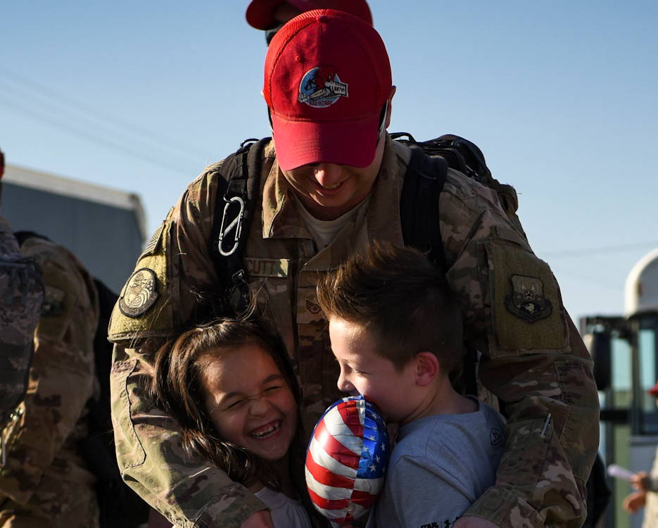 May 2, 2019 - An Airman assigned to the 820th RED HORSE Squadron hugs his children for the first time in six months during a redeployment event at Nellis Air Force Base, Nevada. Friends and family gathered to welcome the Airmen home from their deployment. (Image created by USA Patriotism! from U.S. Air Force photo by Airman 1st Class Bailee A. Darbasie)