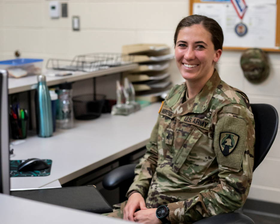 "Sgt. Ayrin Hamner-Ripperger, the administration and supply non-commissioned officer for the 831st Engineer Company, Iowa Army National Guard (IANG), smiles for a photo at her desk at Camp Dodge Joint Maneuver Training Center on May 13, 2019. In September 2018, Hamner-Ripperger decided to run a half marathon in every state. When she's not running, she's doing her part to keep things running smoothly in her unit, whether that be filling out important paperwork or obtaining supplies needed for a drill weekend. Hamner-Ripperger's coworkers are some of her biggest fans as she completes her ""Chasing 50 States"" journey. (U.S. Army National Guard photo by Sgt. Tawny Schmit)"