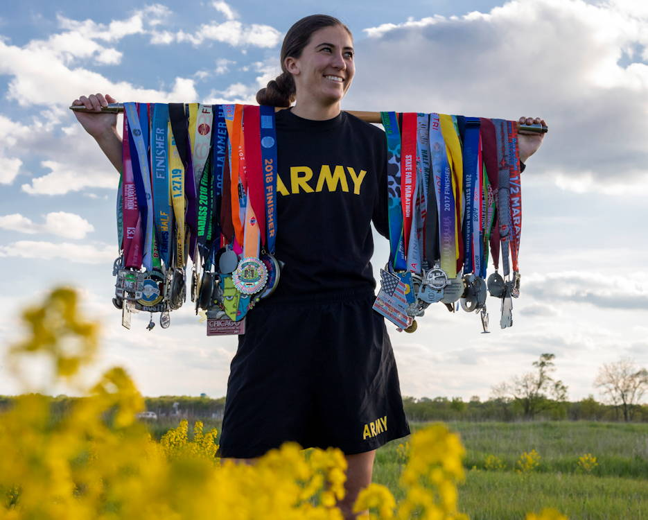 "Sgt. Ayrin Hamner-Ripperger, the administration and supply non-commissioned officer for the 831st Engineer Company, Iowa Army National Guard (IANG), holds the race medals she has earned on her ""Chasing 50 States"" journey on May 13, 2019. After joining the IANG and getting a full-time job at Camp Dodge Joint Maneuver Training Center, Hamner-Ripperger found a passion for running. In September 2018, she decided to run a half marathon in every state. She will check the 50th state off her list when she runs in South Dakota in October 2019. (U.S. Army National Guard photo by Sgt. Tawny Schmit)"
