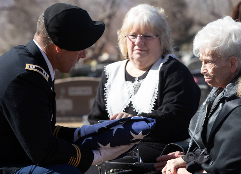 Cpt. Gale Premer, assigned to the 4th Infantry Division, presents a flag to Beverly Miller in honor of her late husband, Maynard Miller, during a full military honors service held at Evergreen Cemetery, Colorado Springs, Colorado, Feb. 12, 2019. The couple was married for 65 years. (U.S. Army photo by Pfc. Matthew Rabahy)