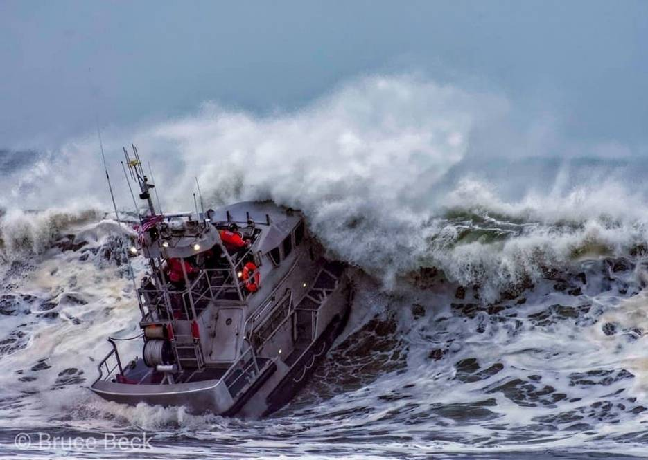 Petty Officer 1st Class Adam Preiser (surfman #535) operates a 47-foot Motor Lifeboat in the surf near Brookings, Oregon, December 13, 2019. Surfman is the pinnacle of the five certifications available to boat-crew members, and Coast Guardsmen. (U.S. Coast Guard photo courtesy of Bruce Beck Photography Public Domain use approved by Mr. Bruce Beck)