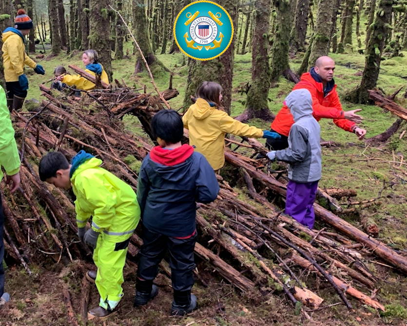 May 16, 2019 - Petty Officer 1st Class Alex Major, a Kodiak-based aviation survival technician, assists North Star Elementary students with building a shelter as part of a survival skills training day on Woody Island, Kodiak, Alaska. Annually, a group of ASTs based in Kodiak travel with the students to Woody Island to teach them basic survival skills essential to life in Alaska. (Image created by USA Patriotism! from U.S. Coast Guard photo by Petty Officer 3rd Class Lauren Dean)