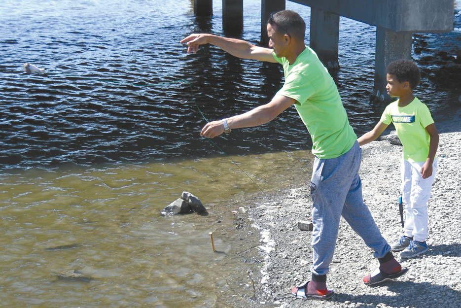 April 27, 2019 - A man and his son toss a chicken leg tied to a string in an attempt to catch a crab at one of the many fishing spots along the Creole Nature Trail. (U.S. Army photo by Chuck Cannon, Fort Polk Public Affairs Office)