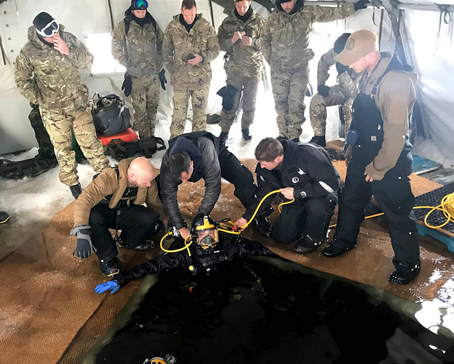 March 12, 2019 - U.S. Navy Chief Builder Adam Perry (standing, right) supervises Construction Mechanic 1st Class John Monahan, both assigned to Underwater Construction Team 1, as hands-on checks of the diver's equipment are competed prior to their descent into a lake during the Royal Canadian Navy's Ice Diving Training Exercise 2019. (U.S. Navy photo by Senior Chief Construction Electrician Terence Juergens)