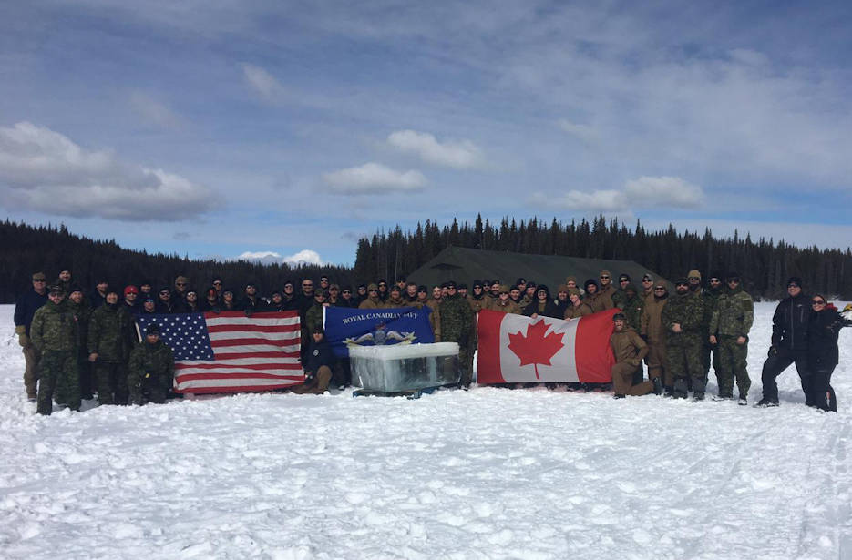March 13, 2019 - U.S. Navy, U.S. Coast Guard, Royal Navy, and Royal Canadian Navy clearance divers stand with a nearly one-ton triangle of 20-inch thick ice during the Royal Canadian Navy's Ice Diving Training Exercise 2019. Over the course of two weeks, clearance divers from Navy Expeditionary Combat Command's Underwater Construction Teams 1 and 2 and Mobile Diving and Salvage Units 1 and 2 joined U.S. Coast Guard, Royal Navy, and Royal Canadian Navy clearance divers to sharpen up their ice diving skills. (U.S. Navy photo by Senior Chief Construction Electrician Terence Juergens)