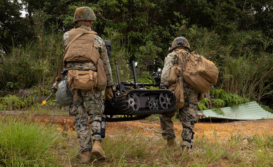 U.S. Marine Corps Staff Sgt. Jeffrey Meyer and Sgt. Joseph Kenney carry a TALON robot to search for ordnance during an explosive ordnance disposal exercise at the Jungle Warfare Training Center, Camp Gonsalves, Okinawa, Japan, September 17, 2019. (U.S. Marine Corps photo by Lance Cpl. Carla Elizabeth O)