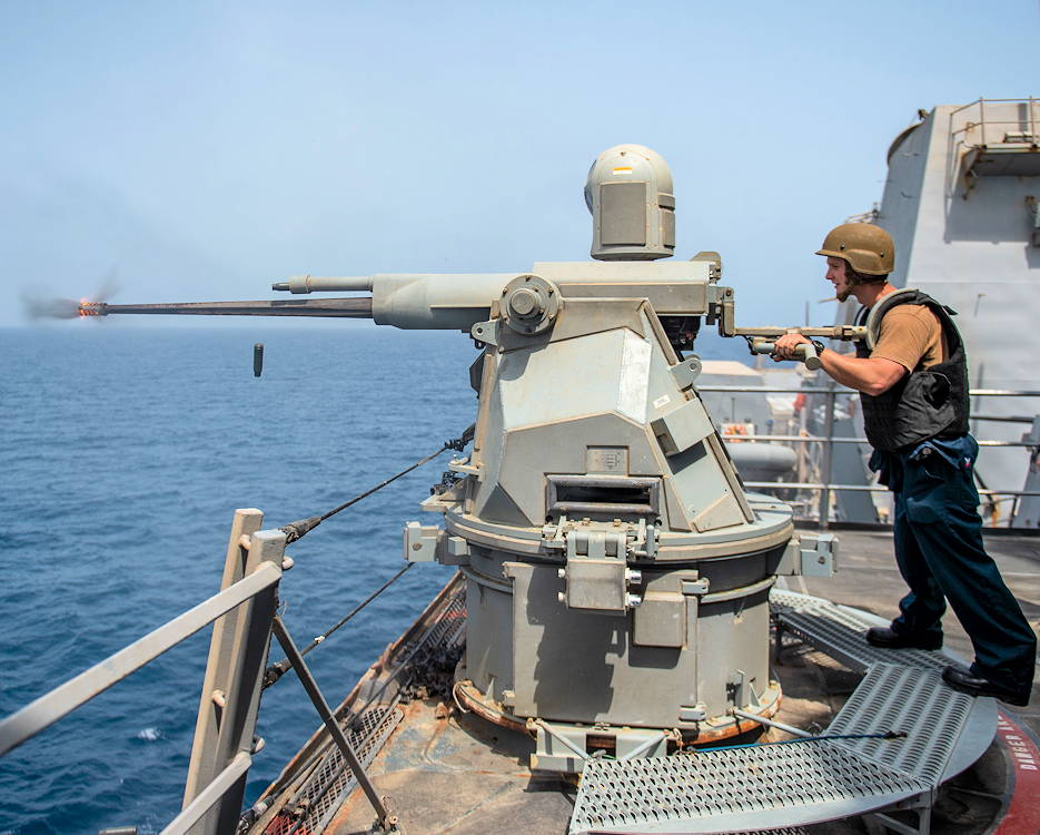 July 29, 2019 - Gunner's Mate 2nd Class Thomas Ricard fires a 25mm machine gun during a live-fire exercise aboard the guided-missile destroyer USS Bainbridge (DDG 96) ... that is deployed to the U.S. 5th Fleet area of operation in support of naval operations to ensure maritime stability and security in the Central Region, connecting the Mediterranean and Pacific through the Western Indian Ocean and three strategic choke points. (U.S. Navy photo by Mass Communication Specialist 3rd Class Jason Waite)