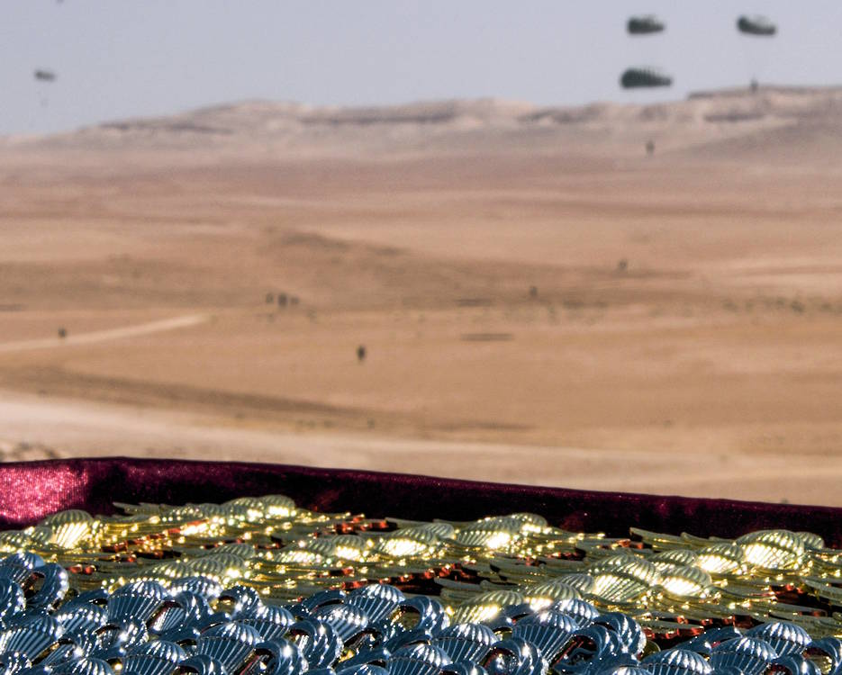 September 5, 2019 - A set of jump wings prepared for the pinning ceremony that takes place after the Friendship Jump remains in focus as the jumper's parachute to the Jordanian ground during Exercise Eager Lion. Eager Lion, U.S. Central Command's largest and most complex exercise, is an opportunity to integrate forces in a multilateral environment, operate in realistic terrain and strengthen military-to-military relationships. (U.S. Air Force photo by Senior Airman Joshua Kincaid)