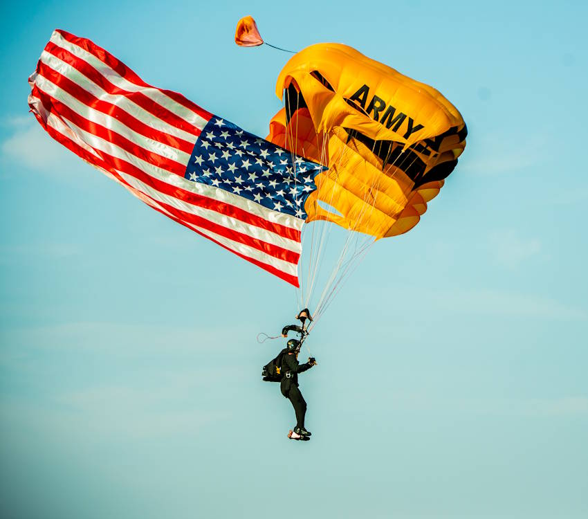 A member of the U.S. Army Parachute Team, commonly known as the Golden Knights, parachutes onto Fryar Drop Zone during the playing of the national anthem. Maneuver Center of Excellence and Fort Benning commemorated the 2019 National Airborne Day on August 16 at Fryar Drop Zone at Fort Benning. (U.S. Army photo by Patrick Albright, Maneuver Center of Excellence, Fort Benning Public Affairs)
