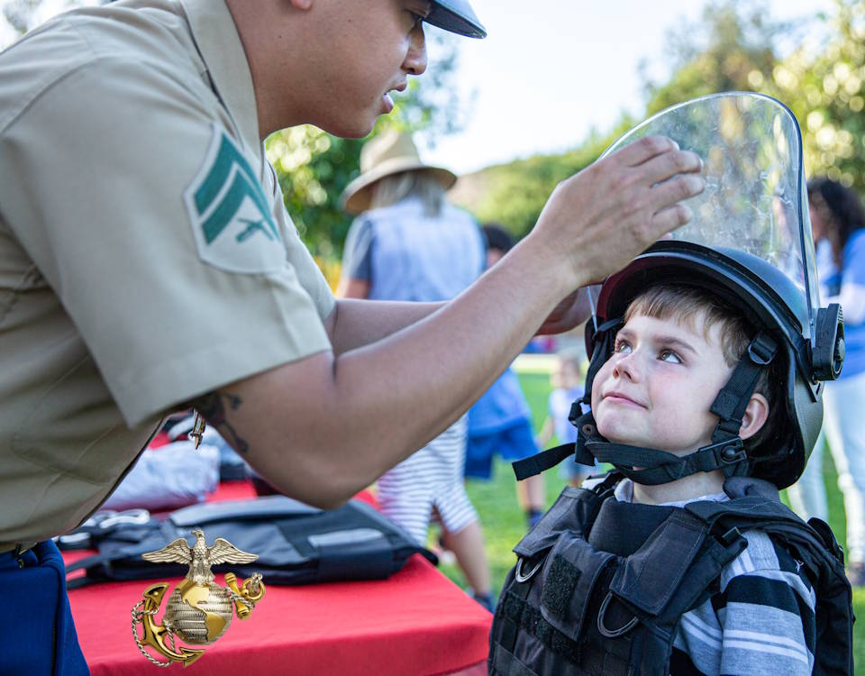 October 17, 2019 - Cpl. Christopher Lim, a Physical Security Specialist with the Marine Corps Air Station Miramar Provost Marshal Office, puts gears on a student at the Pomerado Elementary School in Poway, California. The Marines attended the Pomerado Elementary School's Annual Pomerado Fall Festival to support the involvment with the San Diego community. (Image created by USA Patriotism! from U.S. Marine Corps photo by Lance Cpl. Cheng Chang)