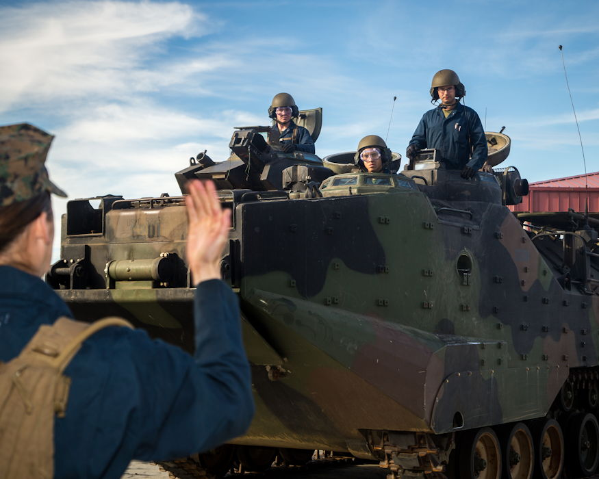 January 28, 2019 - U.S. Marine Corps Pfc. Sarah Brewster, left, student, Assault Amphibian School (AAS) Battalion, Training Command, instructs the operator of an amphibious assault vehicle (AAV) P7/A1 with hand-and-arm signals during ground guidance drills at Marine Corps Base Camp Pendleton, California. The drills were conducted to evaluate the students on ground guidance procedures and techniques when guiding an AAV. (U.S. Marine Corps photo by Cpl. Juan Bustos)