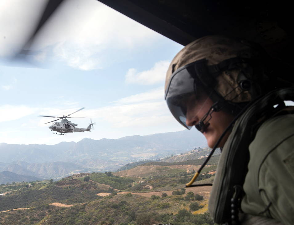 U.S. Marine Corps Sgt. Dalton Hasbrouck, aerial observer, Light Attack Helicopter Squadron (HMLA) 469, Marine Aircraft Group (MAG) 39, 3rd Marine Air Wing (MAW) looks for any strange movement on the ground on Marine Corps Base Camp Pendleton, California on June 25, 2019. CAL training is held for new pilots to get familiar with landing the UH-1Y Venom on tough terrain areas that other aircraft platforms don't have the capability of doing. (U.S Marine Corps photo by Pfc. Andrew Cortez)