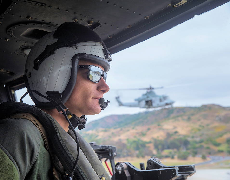 U.S. Marine Corps Sgt. Preston Eisele, weapons and tactics instructor crew chief, Light Attack Helicopter Squadron (HMLA) 469, Marine Aircraft Group (MAG) 39, 3rd Marine Air Wing (MAW) watches the aircrafts surroundings on Marine Corps Base Camp Pendleton, California on June 25, 2019. CAL training is held for new pilots to get familiar with landing the UH-1Y Venom on tough terrain areas that other aircraft platforms don't have the capability of doing. (U.S Marine Corps photo by Pfc. Andrew Cortez)