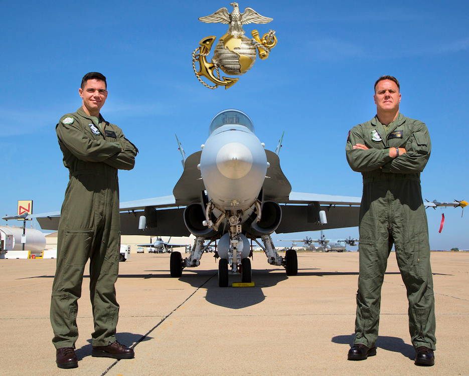 July 27, 2019 - U.S. Marine Corps Lt. Col. Jarrod DeVore, right, and Maj. Jarod Dicks, both F/A-18C Hornet pilots with Marine Fighter Attack Training Squadron (VMFAT) 101, Marine Aircraft Group 11, 3rd Marine Aircraft Wing, pose in front of a Hornet at the San Diego Jet Center, San Diego, California. VMFAT-101 is the largest F/A-18 squadron in the Marine Corps and has over 60 fighter jets attached to the squadron. (Image created by USA Patriotism! from U.S. Marine Corps photo by Sgt. Victoria Decker)