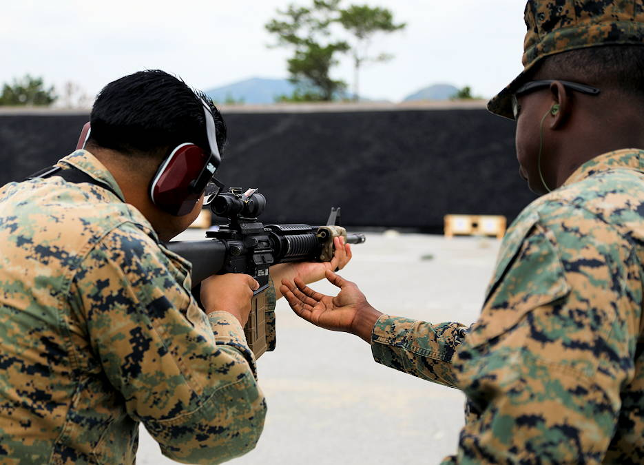 U.S. Marine Corps Cpl. David Millwood, right, from 9th Engineer Support Battalion, corrects Sgt. Roman Acuna Jr., a combat marksmanship trainer, on weapon placement during a practical application test on the Combat Marksmanship Coaching (CMC) course on Camp Hansen, Okinawa, Japan, Oct. 29, 2019. The CMC course develops Marines to be proficient marksmanship coaches in order to enhance combat effectiveness of the Marine Corps. (U.S. Marine Corps photo by Lance Cpl. Alexandria Nowell)